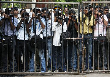 Press photographers in Mumbai stand behind a fence for security reasons as they take pictures of Belgium's Queen Paola in a school in 2008