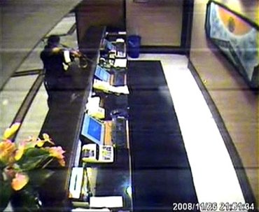 A terrorist aims his weapon at a desk in Trident-Oberoi hotel in this image taken from the hotel's CCTV video footage