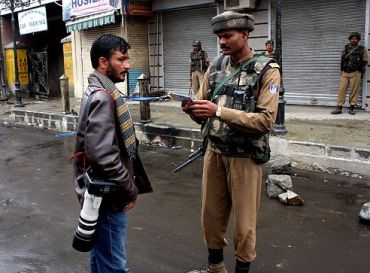 An army jawan checks the credentials of a photographer in Srinagar
