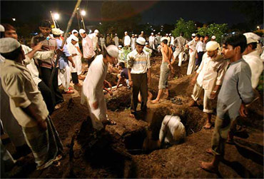 A file photo of people digging graves for blast victims