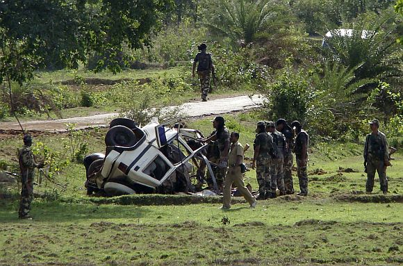 Policemen stand near wreckage of their vehicle after a Maoist attack in West Midnapore district of West Bengal