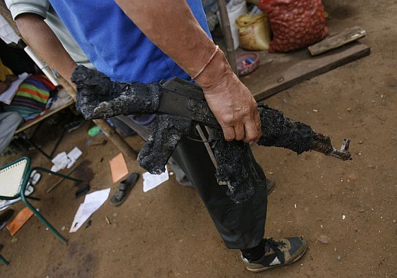 A policeman holds a burnt weapon at a police camp attacked by Maoist rebels in Silda village of West Bengal