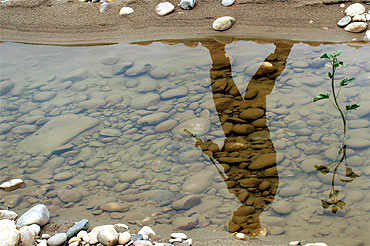 The reflection of a soldier is seen in a puddle