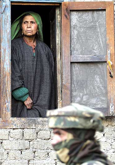 A Kashmiri woman looks out from the window of her house as an army soldier keeps guard