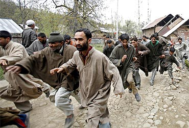 Kashmiri protesters run for cover after army soldiers fired shots into the air to disperse them
