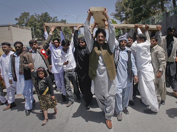 Pakistani Christians carry a cross through the streets of Quetta while observing Good Friday