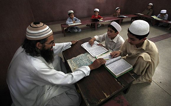 A teacher guides students in reciting verses from the Holy Koran at a mosque in Peshawar.