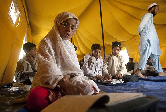 A young girl reads aloud while attending class in a makeshift school tent in Mingora