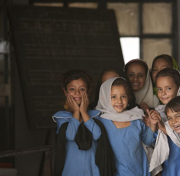 Girls react to their picture being taken from the doorway of a classroom while attending school in Mingora, Pakistan