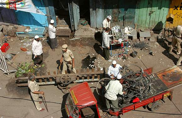 Locals and police officers clear debris at a blast site in Malegaon