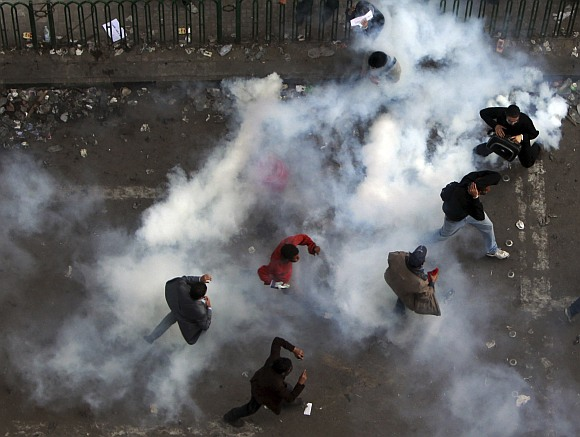 Protesters run from tear gas fired by riot police during clashes along a road which leads to the Interior Ministry, near Tahrir Square