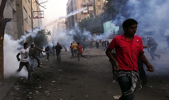 Protesters run from tear gas fired by riot police during clashes along a road which leads to the Interior Ministry, near Tahrir Square in Cairo
