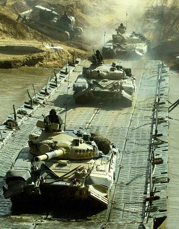 Indian soldiers atop T-72 tanks cross a bridge as they take part in an exercise