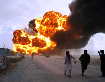 Men run away from burning oil tankers, used to carry fuel for NATO forces in Afghanistan, as they explode after they were attacked on the outskirts of Quetta