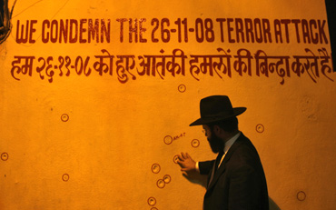 A rabbi touches a wall riddled with bullet holes in front of Nariman House, Mumbai