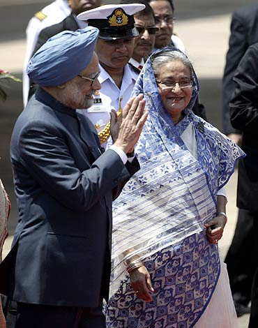 Dr Singh  greets as Bangladesh's Prime Minister Sheikh Hasina watches after they arrive at the Hazrat Shahjalal International Airport in Dhaka September 6