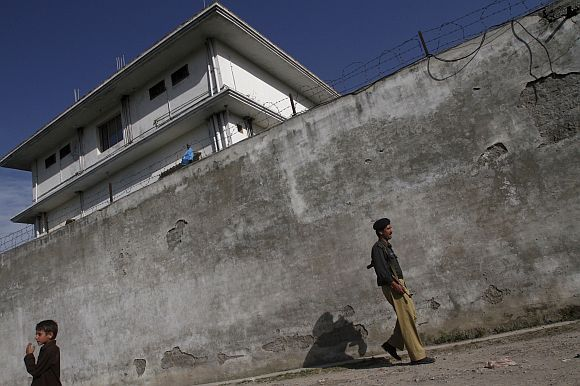 A Pakistani policeman walks in front of the compound where Al Qaeda leader Osama bin Laden was killed in Abbottabad