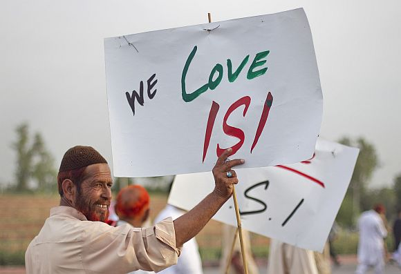 An activist holds a placard as protesters rally in favour of Pakistan's army and Inter-Services Intelligence in Islamabad