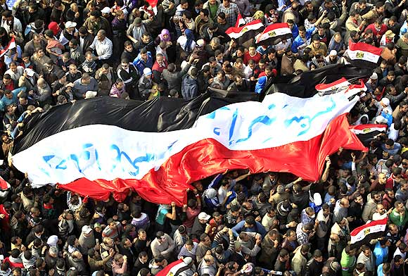 Egyptian protesters march with a huge flag during a rally
