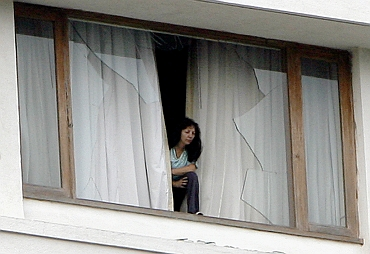 A hotel guest looks out from a broken window of the besieged Trident-Oberoi Hotel in in Mumbai on November 28, 2008