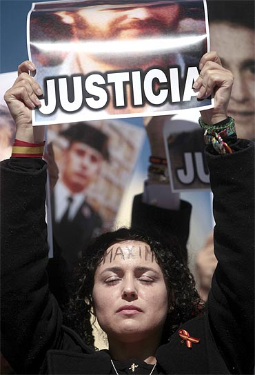 The daughter of a victim of the Basque separatist guerrilla group ETA holds her father's picture during a demonstration in Madrid