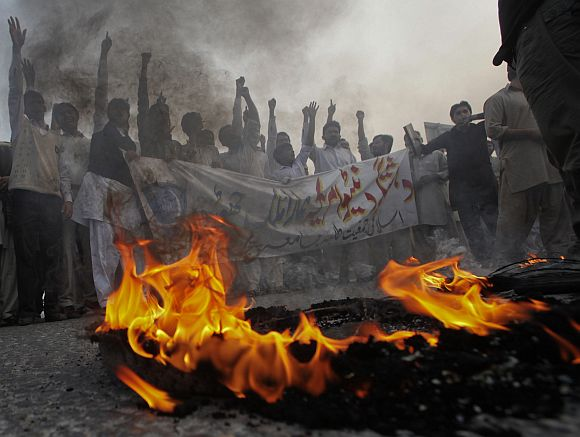 Pakistani students hold a banner while protesting against NATO forces in front of a burning tyre in Lahore