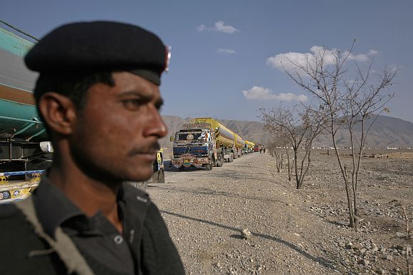 A policeman stands guard near trucks, some of which were carrying supplies to NATO forces in Afghanistan, as they line up in the outskirts of Quetta