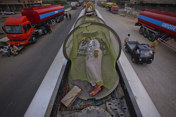 Drivers, some of whom were carrying fuel for NATO forces in Afghanistan, sleep on top of their trucks at a fuel terminal in Karachi