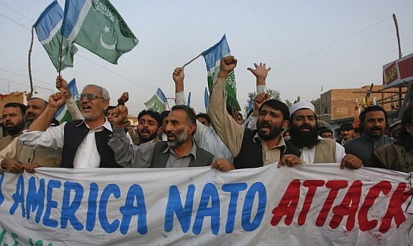 Supporters of religious political party Jamaat-e-Islami hold a banner while demonstrating against NATO