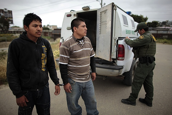 A United States border patrol agent catches illegal immigrants crossing from Mexico to the U S in San Ysidro, California,
