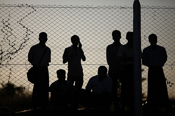 People watch from behind a fence of the airport as Clinton is welcomed upon her arrival to Myanmar's capital Naypyitaw