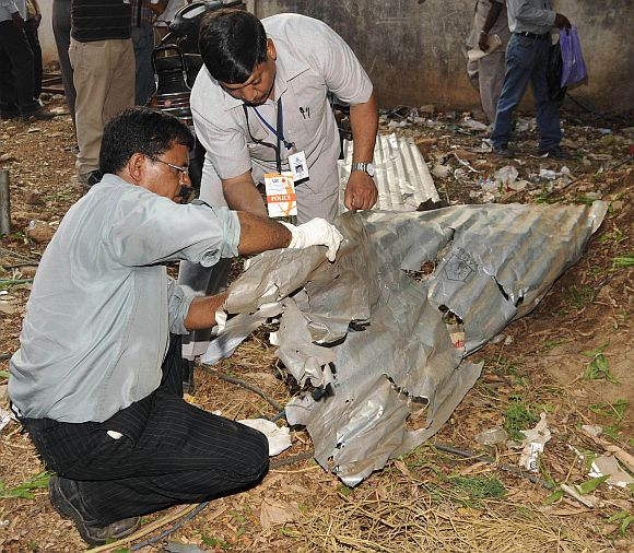 Forensic experts inspect the site of a bomb blast outside the Chinnaswamy cricket stadium in Bengaluru on April 17, 2010.