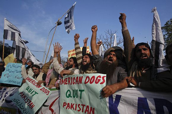 Supporters of Jamaat-ud-Dawa hold placards while shouting ant-American slogans during a demonstration in Lahore on Tuesday