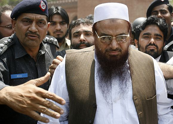 Police escort Hafiz Saeed, the head of the banned Jamaat-ud-Dawa and founder of Lashkar-e-Tayiba