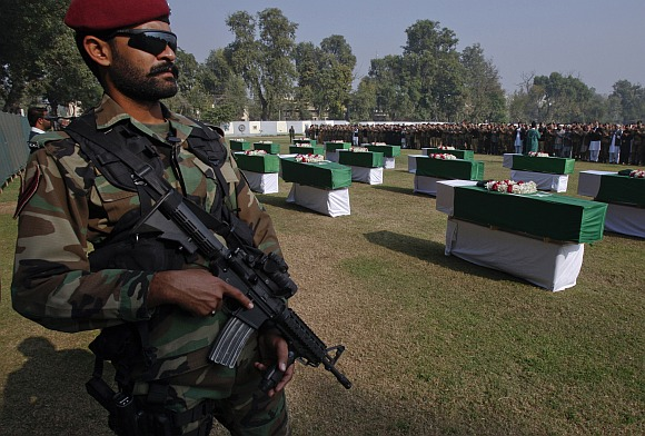 An army soldier stands guard near caskets of soldiers killed in the attack.