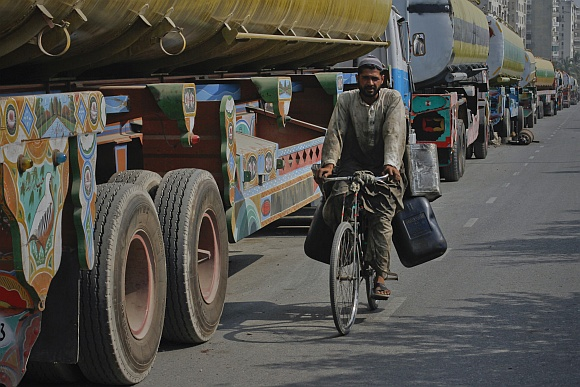 A man rides his bicycle past trucks, some of which are carrying fuel for NATO forces in Afghanistan, lined up along a road in Karachi