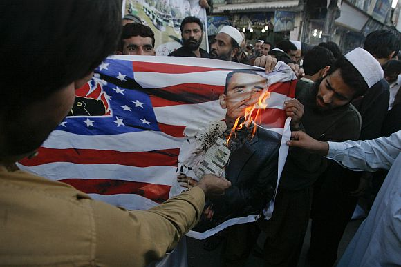 Protesters burn an image of US President Obama printed on the US flag during a demonstration against a NATO cross-border attack in Peshawar