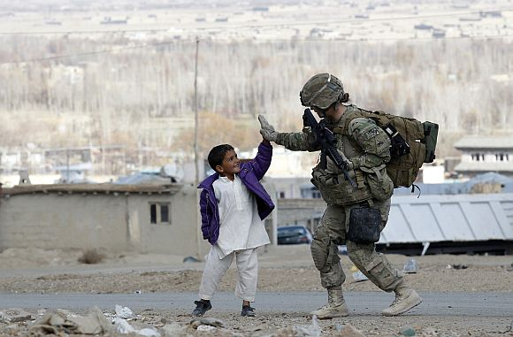 A US soldier takes five with an Afghan boy during a patrol in Pul-e Alam, a town in Logar province, eastern Afghanistan