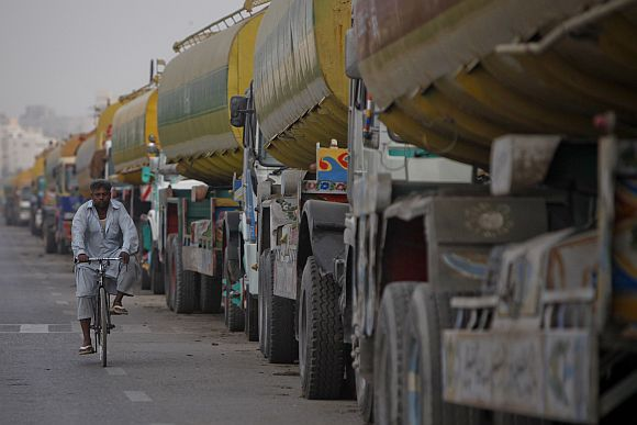 A man rides his bicycle past tankers, carrying fuel for NATO forces, lined up along a road in Karachi, after traffic was halted at the Pakistan-Afghanistan border.