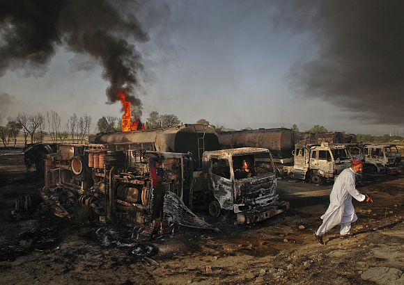 A resident walks past fuel tankers which were set ablaze in Pindi Gheb, some 122 km (76 miles) east of Pakistani capital Islamabad. Gunmen attacked and set fire to eight trucks transporting supplies to NATO forces in Afghanistan in Pakistan's eastern Punjab province