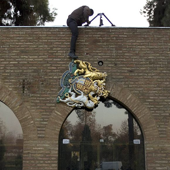 A protesters removes the emblem from the British embassy