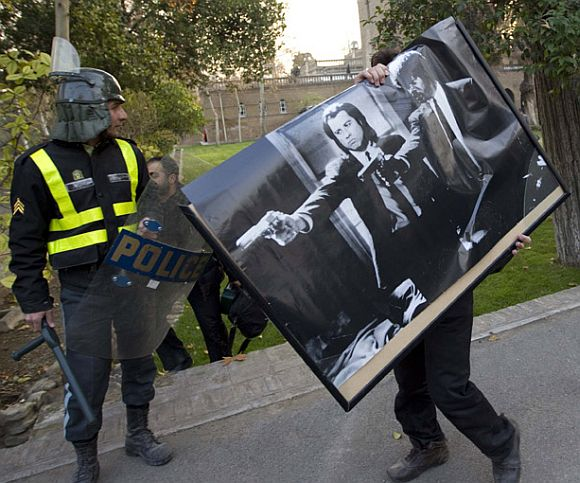 A protester walks away from the embassy with a Pulp Fiction poster