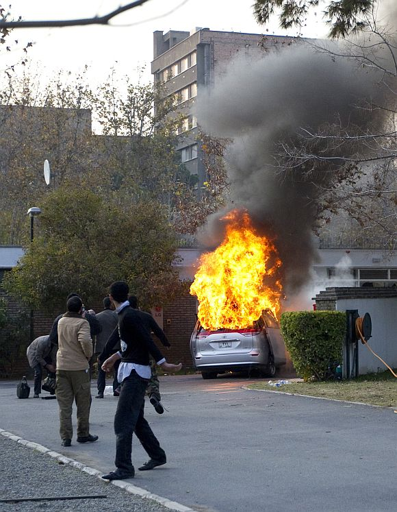 Protesters walk in the British embassy compound as an embassy car burns