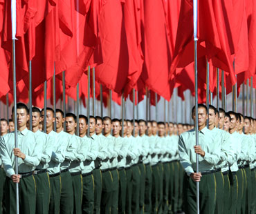 Participants hold red flags during the National Day ceremony at Tiananmen Square in Beijing