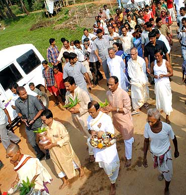Villagers and family members accompany Pranab Mukherjee to a canal of the Kueye river to perfom a ritual