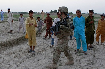 Afghan boys greet a US female soldier from Task Force Bronco 3rd Platoon 307th MP Company while patrolling in a village in Shinwar district in Nangarhar, in this picture taken on September 10, 2011.