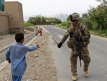A US soldier uses a stick to play swords with a boy during a patrol in Nangharhar