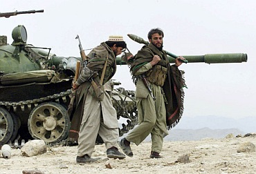 Anti-Taliban Afghan fighters carrying rocket-propelled grenade walk beside a T55 Soviet tank in the Tora Bora mountains