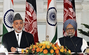 Afghanistan's President Hamid Karzai speaks with the media as Prime Minister Manmohan Singh watches after signing a joint statement at Hyderabad House in New Delhi