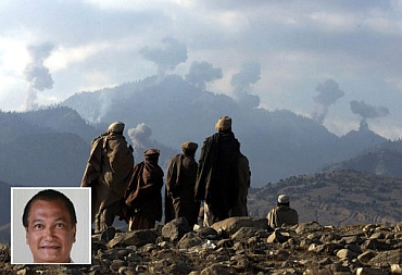 Anti-Taliban Afghan fighters watch several explosions from US bombings in the Tora Bora mountains in Afghanistan in this picture taken on December 16, 2001. (inset) Eric De Castro.